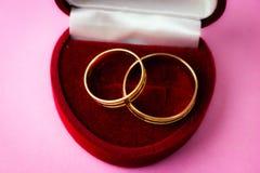 Ένα όμορφο κόκκινο εορταστικό βελούδο κιβωτίων δώρων για δύο δέσμευση, γαμήλια δαχτυλίδια με τα πολύτιμα χρυσά στρογγυλά πολύτιμα στοκ εικόνα