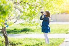 Ένα όμορφο μικρό κορίτσι κρατά μια κάμερα στα χέρια της στοκ φωτογραφίες με δικαίωμα ελεύθερης χρήσης