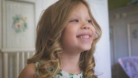 Ένα όμορφο μικρό κορίτσι χαμογελά στο φωτεινό δωμάτιο απόθεμα βίντεο