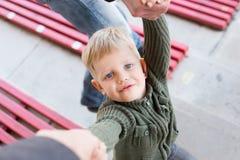Ένα όμορφο μικρό παιδί που εξετάζει επάνω τους γονείς του, που κρατούν τα χέρια Στοκ εικόνα με δικαίωμα ελεύθερης χρήσης