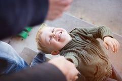 Ένα όμορφο μικρό παιδί που εξετάζει επάνω το γονέα του, που κρατά τα χέρια Στοκ Εικόνες