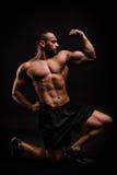 Ένα όμορφο, μυϊκό προκλητικό άτομο σε ένα μαύρο υπόβαθρο Ένα bodybuilder θέτει σε ένα στούντιο Αθλητική έννοια στοκ εικόνες με δικαίωμα ελεύθερης χρήσης