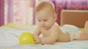 Ένα όμορφο μωρό βρίσκεται Κρατά τη σφαίρα στο χέρι του και παίζει με την απόθεμα βίντεο