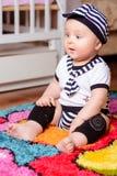 Ένα όμορφο μωρό σε ένα ριγωτό πουκάμισο και τα καπέλα που κάθονται στο χαλί στο δωμάτιο στοκ εικόνες με δικαίωμα ελεύθερης χρήσης