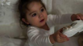 Ένα όμορφο μωρό στο λίκνο εξετάζει τα νέα παπούτσια της απόθεμα βίντεο