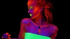 Ένα όμορφο νέο ημίγυμνο κορίτσι που χορεύει με το καμμένος χρώμα στο σώμα της στο μαύρο φως Όμορφη γυναίκα με την πυράκτωση απόθεμα βίντεο