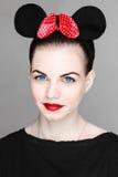 Ένα όμορφο νέο κορίτσι με ένα όμορφο τόξο με τα σημεία Πόλκα και τα αυτιά ποντικιών στο στούντιο σε ένα γκρίζο υπόβαθρο Στοκ φωτογραφία με δικαίωμα ελεύθερης χρήσης