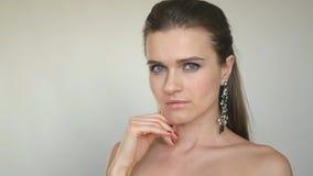 Ένα όμορφο νέο κορίτσι με τους καλλωπισμούς στα αυτιά του, στάσεις σε ένα άσπρο υπόβαθρο στην τοποθέτηση στούντιο για τη κάμερα στοκ εικόνα