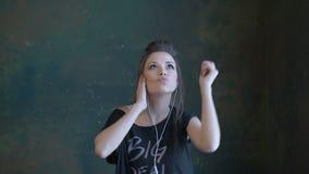 Ένα όμορφο νέο κορίτσι που χορεύει στη μουσική απόθεμα βίντεο