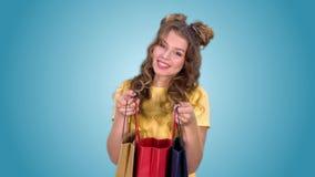 Ένα όμορφο νέο κορίτσι σε μια κίτρινη μπλούζα μετά από να ψωνίσει ανοίγει τη συσκευασία και απολαμβάνει απόθεμα βίντεο