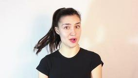Ένα όμορφο νέο κορίτσι σε μια μαύρη μπλούζα λέει το αριθ. και τινάζει το κεφάλι της στον αρνητικό απόθεμα βίντεο