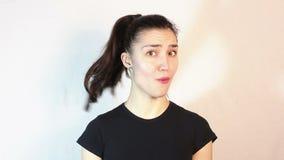 Ένα όμορφο νέο κορίτσι σε μια μαύρη μπλούζα λέει το αριθ. και τινάζει το κεφάλι της στον αρνητικό φιλμ μικρού μήκους