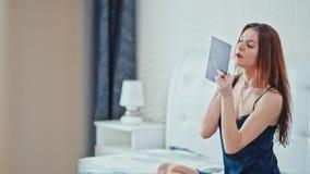 Ένα όμορφο νέο κορίτσι χρωματίζει τα χείλια της, καθμένος στο κρεβάτι στην κρεβατοκάμαρα απόθεμα βίντεο