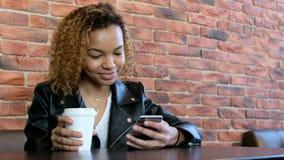 Ένα όμορφο νέο μαύρο κορίτσι σε ένα σακάκι δέρματος με ένα άσπρο ποτήρι του καφέ και του κινητού τηλεφώνου κάθεται σε έναν πίνακα απόθεμα βίντεο