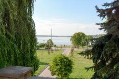 Ένα όμορφο πάρκο με τα διακοσμητικά δέντρα και ένα όμορφο ανάχωμα με μια αποβάθρα Στοκ Εικόνες