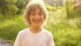 Ένα όμορφο σγουρός-μαλλιαρό αγόρι στέκεται κάτω από τη θερινή θερμή βροχή και χαμογελά Ημέρα παιδιών happy holidays απόθεμα βίντεο