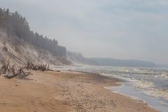 Ένα όμορφο τοπίο παραλιών σε μια θυελλώδη ημέρα, φυσώντας άμμος αέρα μέχρι τους υψηλούς αμμώδεις απότομους βράχους Τοπίο άνοιξη σ Στοκ φωτογραφίες με δικαίωμα ελεύθερης χρήσης
