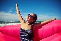 Ένα όμορφο χαμόγελο και κράτημα των χεριών της επάνω στη γυναίκα στην παραλία Στοκ Φωτογραφία