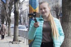 Ένα όμορφο blogger που πυροβολεί το βίντεο στην οδό, χρησιμοποιώντας ένα τηλέφωνο και ένα ραβδί selfie στοκ φωτογραφίες