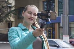Ένα όμορφο blogger πυροβολεί ένα βίντεο στην οδό, χρησιμοποιώντας ένα τηλέφωνο και ένα ραβδί selfie στοκ φωτογραφία με δικαίωμα ελεύθερης χρήσης