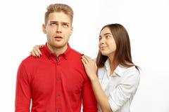 Ένα όμορφο brunette σε ένα άσπρο πουκάμισο αγκαλιάζει και καθησυχάζει το σύντροφό της - ένας νεαρός άνδρας με τα ξανθά μαλλιά που στοκ φωτογραφίες με δικαίωμα ελεύθερης χρήσης