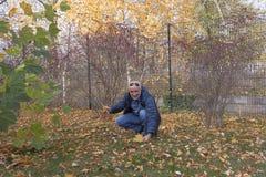 Ένα ώριμο άτομο έσκυψε στη χλόη με τα πεσμένα φύλλα στοκ εικόνες με δικαίωμα ελεύθερης χρήσης