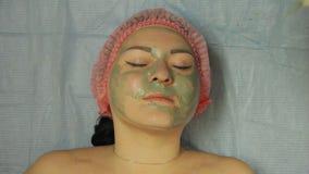 Ένα beautician στα γάντια αφαιρεί μια μάσκα από το πρόσωπο μιας γυναίκας με έναν δίσκο βαμβακιού φιλμ μικρού μήκους