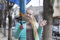 Ένα blogger πυροβολεί ένα βίντεο στην οδό, χρησιμοποιώντας ένα τηλέφωνο και ένα ραβδί selfie στοκ φωτογραφίες με δικαίωμα ελεύθερης χρήσης