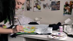 Ένα brunette εφαρμόζει το ρόδινο χρώμα με μια βούρτσα στο ύφασμα Μια απεικόνιση ενός τεριέ ταύρων απεικονίζεται στο σακάκι απόθεμα βίντεο