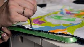 Ένα brunette εφαρμόζει το ρόδινο χρώμα με μια βούρτσα στο ύφασμα Μια απεικόνιση ενός τεριέ ταύρων απεικονίζεται στο σακάκι φιλμ μικρού μήκους