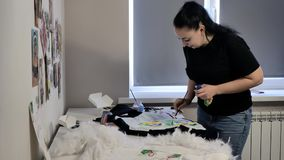 Ένα brunette σε μια μαύρη μπλούζα και τα τζιν σύρει απόθεμα βίντεο