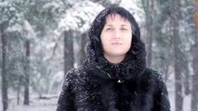 Ένα brunette σε ένα παλτό γουνών στέκεται σε ένα χειμερινό πάρκο και εξετάζει το μειωμένο χιόνι, σε σε αργή κίνηση απόθεμα βίντεο