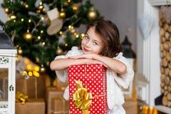 Ένα brunette gilr μπροστά από το γούνα-δέντρο και την εστία με τα κεριά και τα δώρα Να ονειρευτεί κοριτσιών Νέα παραμονή έτους `  στοκ φωτογραφίες