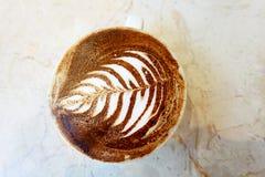 Ένα café latte ότι ένας αριθμός λουλουδιών που επισύρεται την προσοχή στον αφρό στην κορυφή του Στοκ εικόνα με δικαίωμα ελεύθερης χρήσης