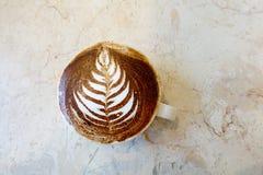 Ένα café latte ότι ένας αριθμός λουλουδιών που επισύρεται την προσοχή στον αφρό στην κορυφή του Στοκ Φωτογραφίες