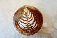 Ένα café latte ότι ένας αριθμός λουλουδιών που επισύρεται την προσοχή στον αφρό στην κορυφή του Στοκ εικόνες με δικαίωμα ελεύθερης χρήσης
