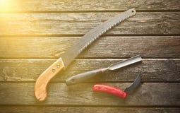 Ένα carpenter& x27 εργαλείο εργασίας του s σε έναν ξύλινο πίνακα Πριόνι, δεκάρες, μαχαίρι, τοπ άποψη στοκ φωτογραφία