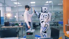 Ένα cyborg και ένα άτομο αγγίζουν το ένα το άλλο χέρι ` s και κοιτάζουν γύρω απόθεμα βίντεο
