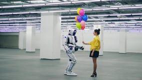 Ένα cyborg λαμβάνει μια δέσμη των μπαλονιών από μια γυναίκα απόθεμα βίντεο