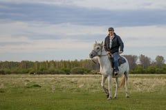 Ένα fermer σε ένα άσπρο άλογο στον τομέα στοκ φωτογραφίες