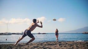 Ένα frisbee παιχνιδιού νεαρών άνδρων στην παραλία με τη φίλη του απόθεμα βίντεο
