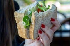 Ένα girl& x27 χέρι του s που κρατά ένα σάντουιτς Στοκ Φωτογραφία