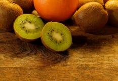 Ένα kiwifruit που χωρίζεται στο μισό βρίσκεται σε έναν ξύλινο τέμνοντα πίνακα στοκ εικόνα με δικαίωμα ελεύθερης χρήσης