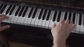 Ένα pianist ατόμων παίζει το πιάνο φιλμ μικρού μήκους