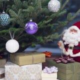 Ένα santa και δώρα παιχνιδιών κάτω από το διακοσμημένο χριστουγεννιάτικο δέντρο Στοκ εικόνα με δικαίωμα ελεύθερης χρήσης