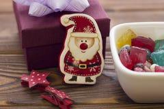 Ένα santa παιχνιδιών, ένα κύπελλο των καραμελών και ένα κιβώτιο δώρων Στοκ φωτογραφία με δικαίωμα ελεύθερης χρήσης