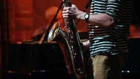 Ένα saxophone παιχνιδιού ατόμων σε έναν φραγμό τζαζ, ένα άλλο άτομο που παίζει τα κλειδιά στην πλάτη απόθεμα βίντεο