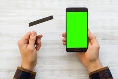 Ένα smartphone με την πράσινη οθόνη για βασικό χρώματος και μια πιστωτική κάρτα στα χέρια ενός ατόμου σε ένα άσπρο υπόβαθρο Στοκ Φωτογραφίες