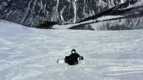 Ένα snowboarder κάθεται στο λόφο και μιλά στο τηλέφωνο πρίν ζαλίζει το βουνό, 4k απόθεμα βίντεο