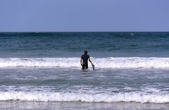 Ένα surfer με τον πίνακά του που πηγαίνει στη θάλασσα στοκ εικόνες